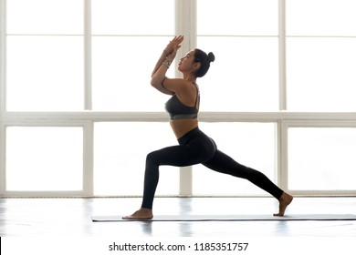 Young sporty attractive woman practicing yoga, doing Warrior one exercise, Virabhadrasana 1 pose with namaste, working out, wearing sportswear, grey pants, top, indoor full length, at yoga studio