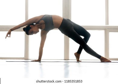 Young sporty attractive woman practicing yoga, doing Wild Thing, Flip-the-Dog exercise, Camatkarasana pose, working out, wearing sportswear, grey pants, top, indoor full length, at yoga studio