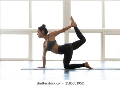 Young sporty attractive woman practicing yoga, doing tiger exercise, Bird dog pose, working out, wearing sportswear, grey pants, bra, indoor full length, at yoga studio