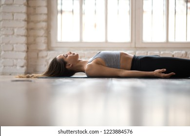 Young sporty attractive woman practicing yoga, doing Dead Body, Savasana exercise, Corpse pose, working out, wearing sportswear, black pants and top, indoor close up, white yoga studio