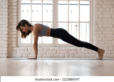 Young sporty attractive woman practicing yoga, doing Push ups or press ups exercise, phalankasana, Plank pose, working out, wearing sportswear, indoor full length, yoga studio