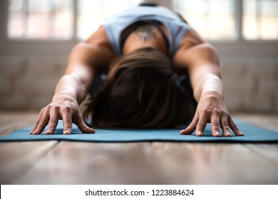 Young sporty attractive woman practicing yoga, doing Child exercise, Balasana pose, working out, wearing sportswear, indoor close up, at yoga studio or at home. Well being concept