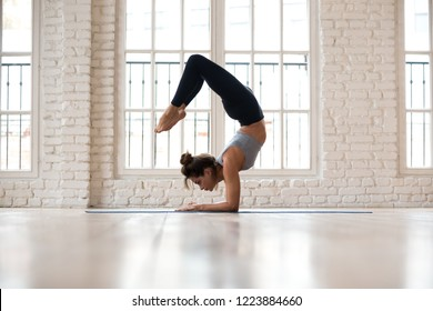 Young sporty attractive woman practicing yoga, doing Vrischikasana, Scorpion exercise, handstand pose, working out, wearing sportswear, pants and top, indoor full length, yoga studio