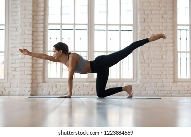 Young sporty attractive woman practicing yoga, doing Donkey Kick exercise, Bird dog pose, working out, wearing sportswear, black pants and top, indoor full length, white yoga studio
