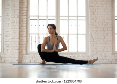 Young sporty attractive woman practicing yoga, doing Head to Knee Forward Bend exercise, Janu Sirsasana pose, working out, wearing sportswear, pants and top, indoor full length, white yoga studio