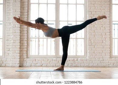 Young sporty attractive woman practicing yoga, doing Warrior III exercise, Virabhadrasana 3 pose, working out, wearing sportswear, black pants and top, indoor full length, white yoga studio