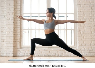 Young sporty attractive woman practicing yoga, doing Warrior Two exercise, Virabhadrasana 2 pose, working out, wearing sportswear, black pants and top, indoor full length, white yoga studio