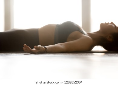 Young sporty attractive woman practicing yoga, doing Dead Body exercise, Savasana, Corpse pose, working out, wearing sportswear, grey top, indoor close up, at yoga studio, side view