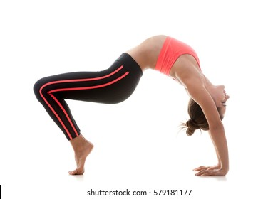 Young sporty attractive woman practicing yoga, stretching in Reverse Table Top exercise, Bridge pose, working out, wearing sportswear, red bra, black pants, full length, white studio background