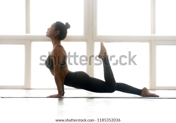 Young sporty attractive woman practicing yoga, doing upward facing dog exercise, Urdhva mukha shvanasana pose, working out, wearing sportswear, grey pants, top, indoor full length, at yoga studio