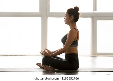 Young sporty attractive yogi woman doing Easy Seat yoga exercise, Sukhasana pose, working out, wearing sportswear grey pants, indoor full length, white at yoga studio, side view. Hobby concept