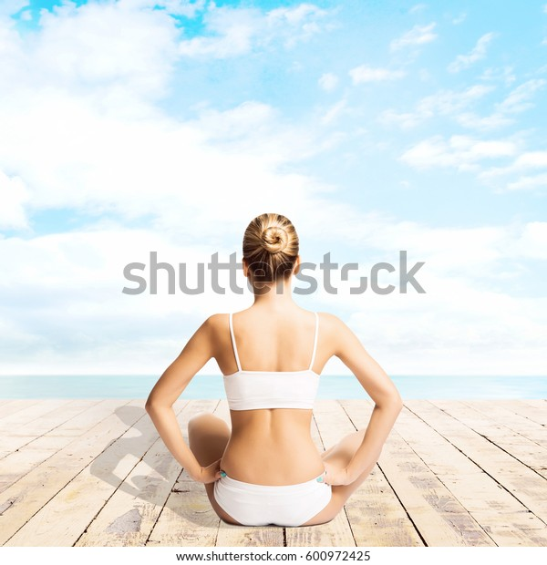 Young, sporty and beautiful girl meditating on a pier at summer. Yoga concept.
