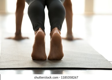 Young sporty beautiful woman practicing yoga, doing Push ups or press ups exercise, phalankasana, Plank pose, working out, wearing sportswear, indoor close up, at yoga studio