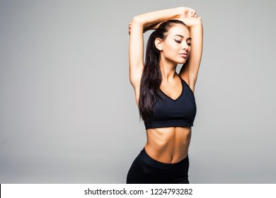 Young sporty beautiful woman stretching arms on side. Full body length portrait isolated over white background.