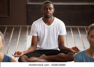 Young sporty black man practicing yoga lesson, sitting in Sukhasana exercise, Easy Seat pose with mudra gesture, students training in club, working out