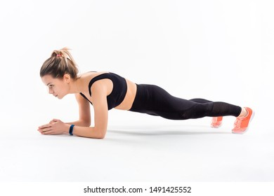 Young sporty blond woman in a black sportswear holding plank position exercising isolated over white background.