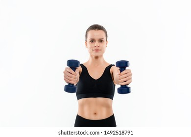 Young sporty blond woman in a black sportswear exercising with hand weights isolated over white background. Muscle-building exercises.