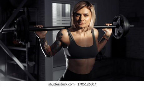 Young sporty blonde woman doing heavy barbell exercise in fitness class.