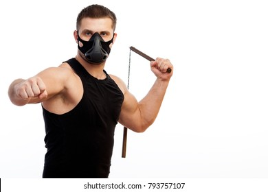 A young sporty blue-eyed man in a sporty black T-shirt, wearing boxing gloves and a black training mask is holding a metal nunchak in his hand on a white isolated background