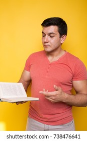 young sporty brunette guy holds in hands books. emotional portrait. clear skin and short hair. street style: jeans and a colored t-shirt