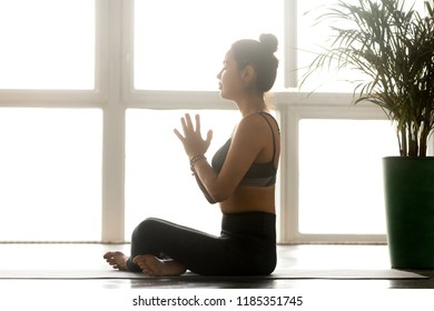 Young sporty calm yogi yoga woman doing Easy Seat exercise, Sukhasana pose, working out in white at yoga studio or at home, wearing grey pants, indoor full length. Hobby wellbeing activity concept