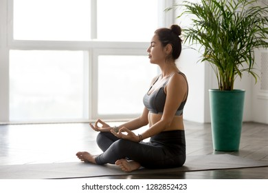 Young sporty calm yogi yoga woman doing Easy Seat exercise, Sukhasana pose, working out, wearing sportswear, grey pants, top, indoor full length, at yoga studio. Hobby wellbeing activity concept