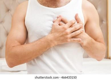 Young sporty Caucasian man in white shirt holds hands near his heart, heart pain gesture