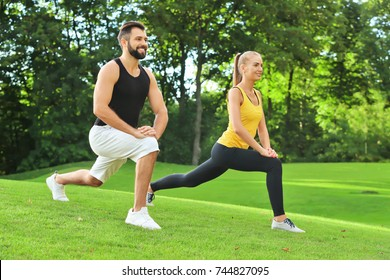 Young sporty couple doing exercise in green park
