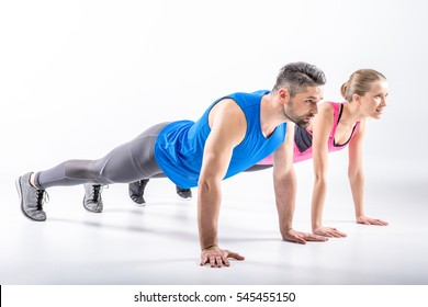 Young sporty couple doing plank exercise together isolated on white