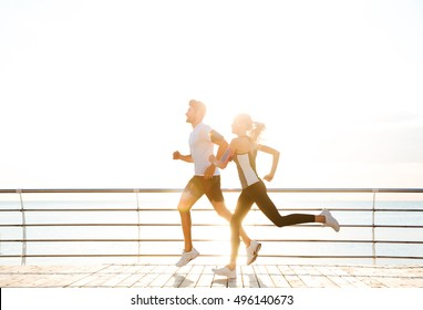 Young sporty couple running over wooden pier at sunset