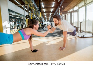 Young sporty couple working out together in a gym . Doing plank exercises while holding each other for one hand.