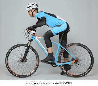 Young sporty cyclist riding bicycle on grey background
