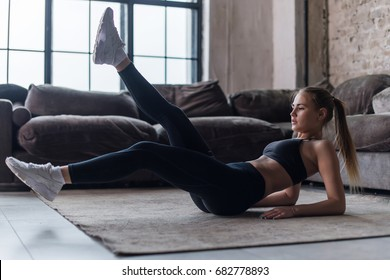 Young sporty female doing abs workout in living room performing alternate leg raising and crunch exercise