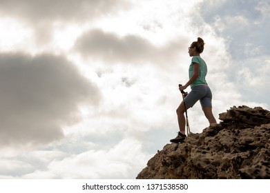 Young and sporty female hiker standing on the rocks with walking sticks