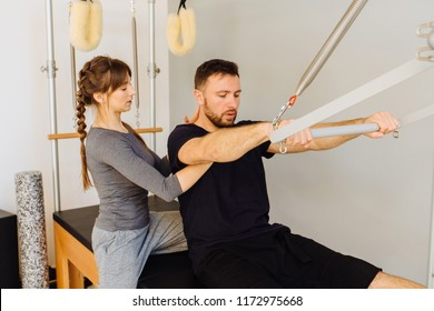 Young sporty female instructor of pilates helping beard man workout in cadillac bed. Two people working in pilates studio, woman assistant supporting and correcting male patient beginner.