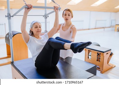 Young sporty female instructor of pilates helping elderly woman workout in cadillac bed. Two people working in pilates studio, woman assistant supporting and correcting old lady patient beginner.