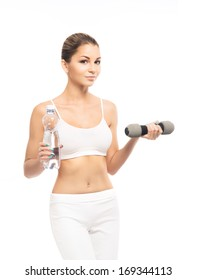 Young, sporty, fit and beautiful girl with the dumbbell and the bottle of water isolated on white