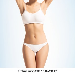 Young, sporty, fit and beautiful girl in sporty underwear over gradient blue background.