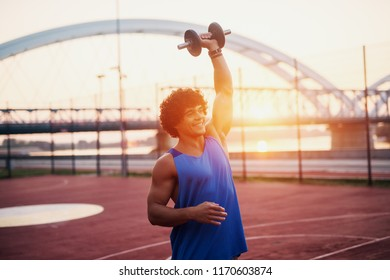 Young sporty fit man holding weight in his arm . Outside early morning training.