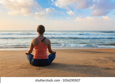 Young sporty fit woman doing yoga - meditating and relaxing in Padmasana Lotus Pose) with chin mudra outdoors at tropical beach on sunset