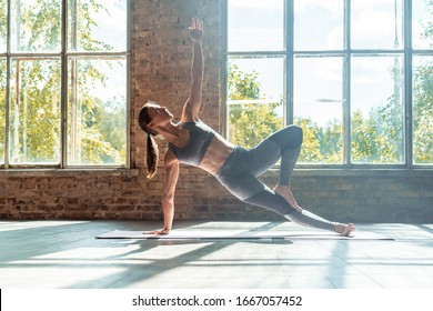 Young sporty fit woman trainer do practice individual hatha yoga instructor training Vasisthasana side plank,arm leg support balancing pose modern gym mat wooden floor window healthy lifestyle concept - Shutterstock ID 1667057452