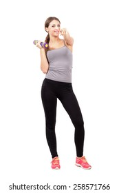 Young sporty fitness woman holding dumbbell pointing at you. Full body length portrait isolated over white background.