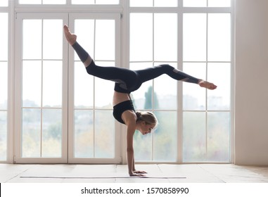 Young sporty flexible woman practicing yoga, doing handstand pose with splitted legs, indoor full length, yoga studio, free space