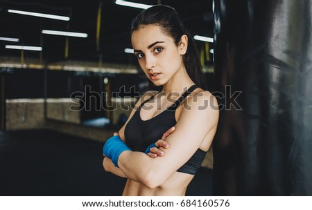 55f8dcd366c Young sporty girl with crossed arms seriously looking at camera. Focused woman  standing with wrapped