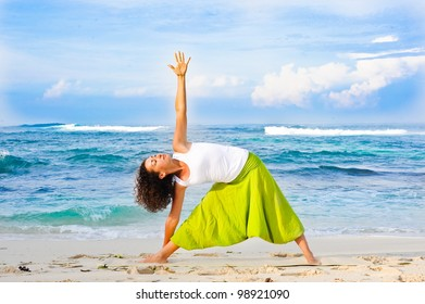 Young sporty girl doing yoga on the beach