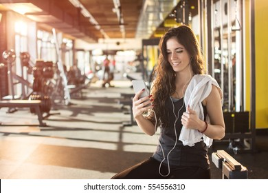 Young sporty girl with earphone listening to music on smartphone in gym.