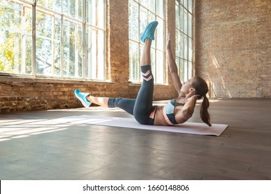 Young sporty girl fitness trainer do hand to big toe reach abdominal weightloss exercise flat belly burn calories fat mat stretch modern spacious gym wooden floor healthy lifestyle concept copy space.