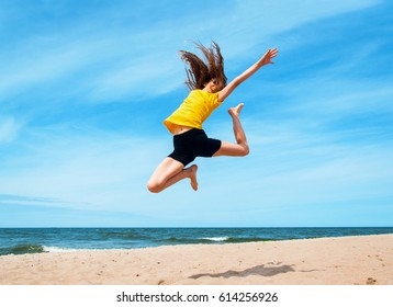 Young sporty girl jumping at the beach