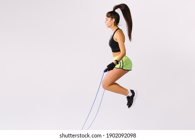 Young sporty girl jumping rope on white background with empty side space.
