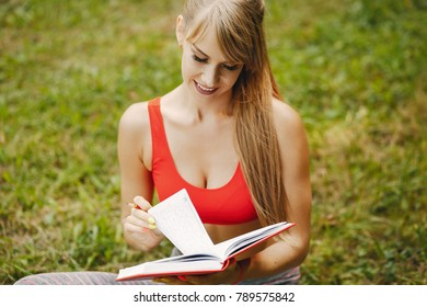 A young and sporty girl in a red sports bra top sitiing on the grass in a summer park and planning her workouts in a notebook.